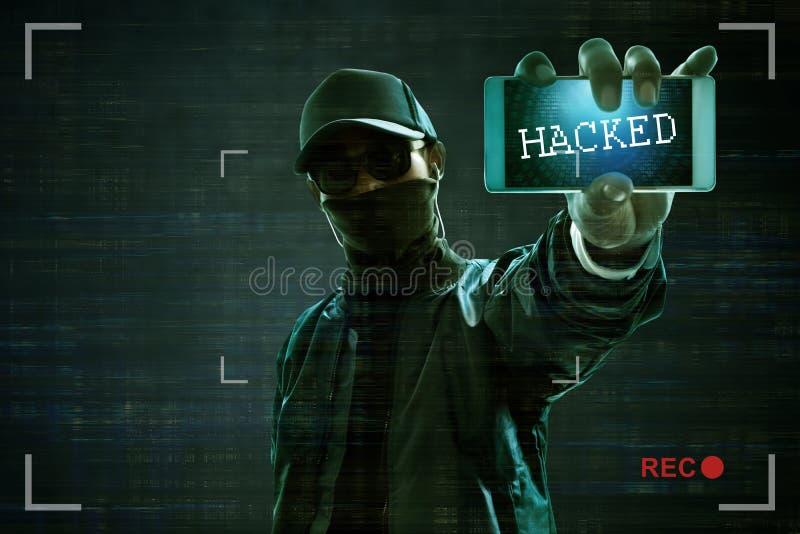 拿着手机的匿名黑客 免版税库存图片