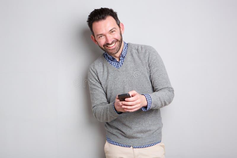 拿着手机的商人反对灰色背景 免版税库存图片