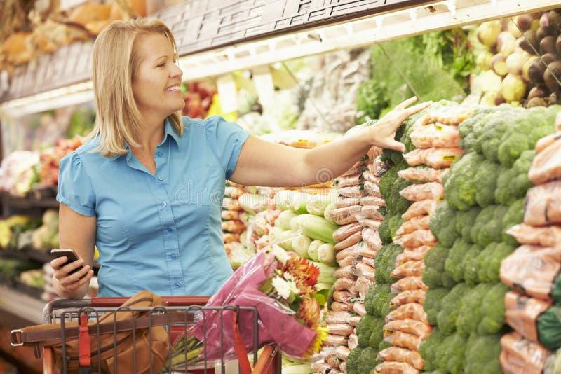 拿着手机的妇女在超级市场 免版税库存图片