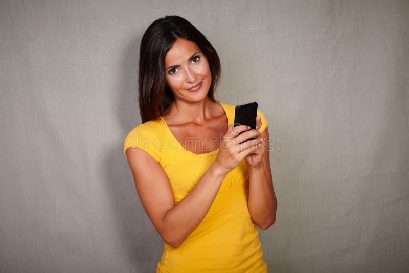 拿着手机的悦目深色的妇女 库存图片