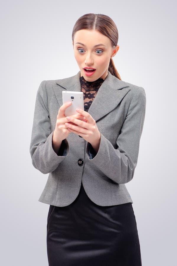 拿着手机的惊奇的年轻女商人 免版税库存照片