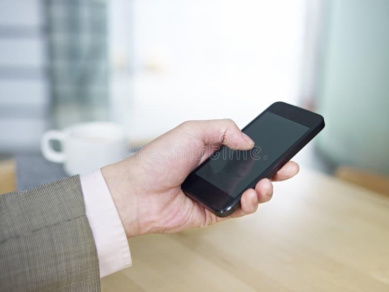拿着手机的手 免版税库存图片