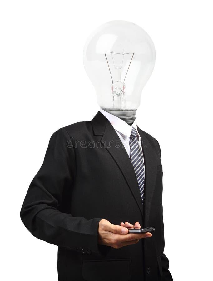 拿着手机的灯顶头商人 免版税库存图片