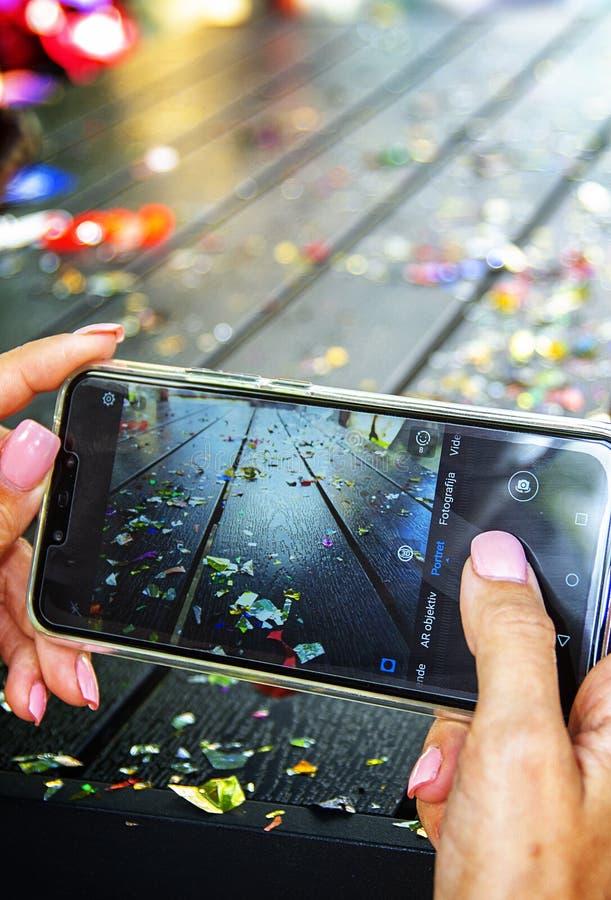 拿着手机的特写镜头妇女在党以后 免版税库存图片