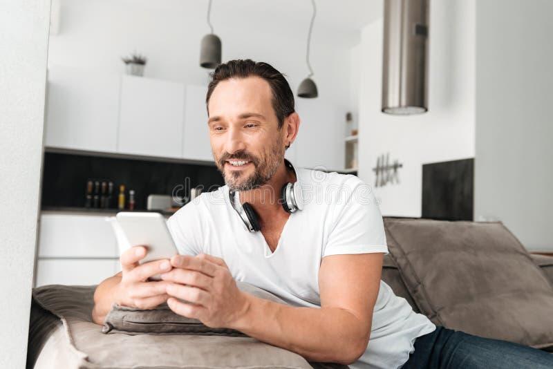拿着手机的英俊的成熟人 库存照片