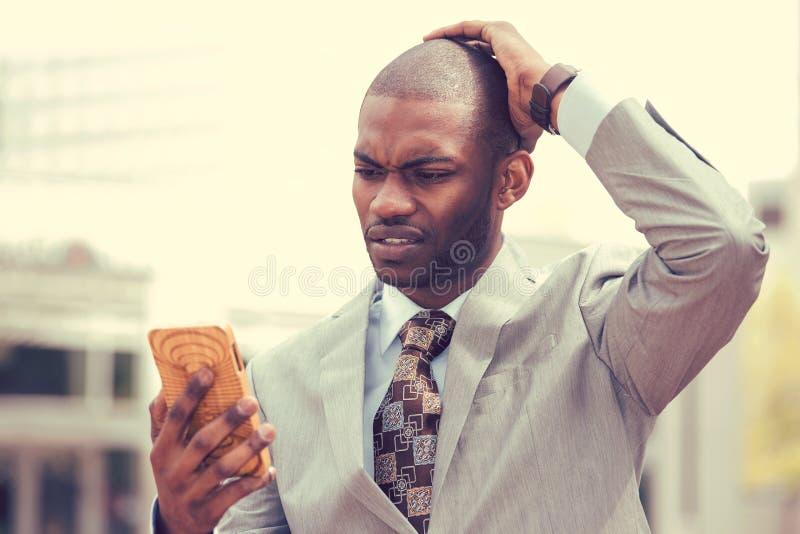 拿着手机的被注重的人看有发怒面孔表示的屏幕 免版税库存图片