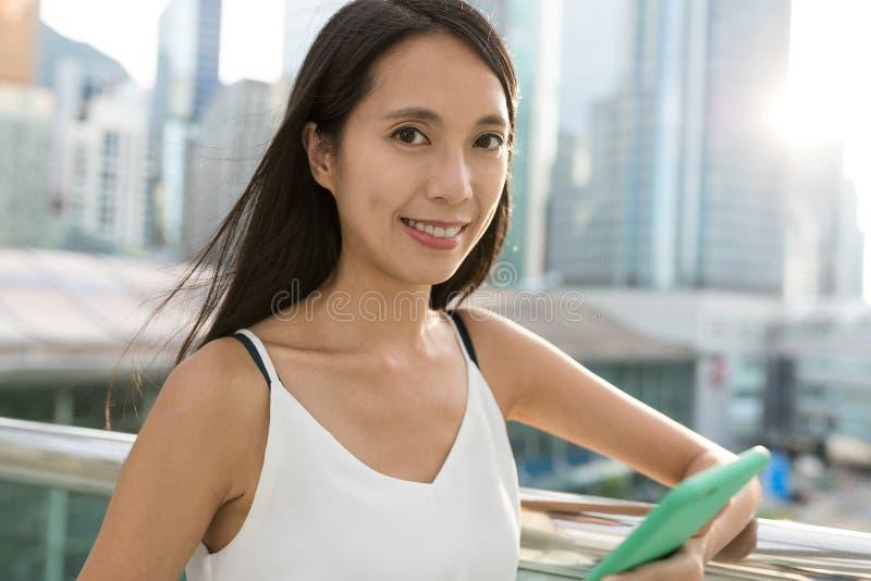 拿着手机的年轻亚裔妇女在城市 免版税库存图片