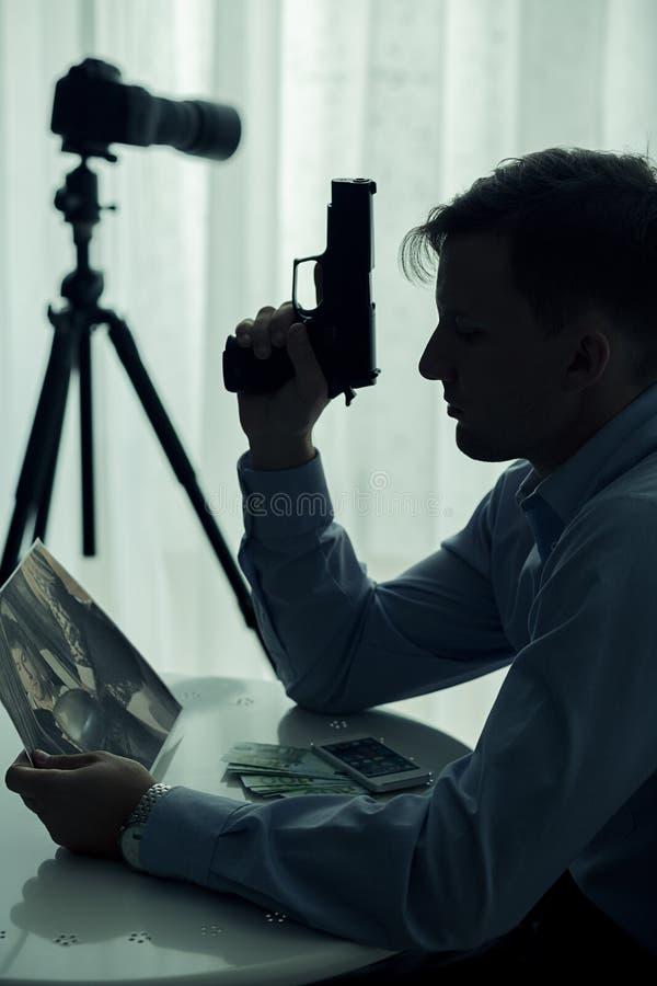 拿着手枪的凶手 免版税库存照片