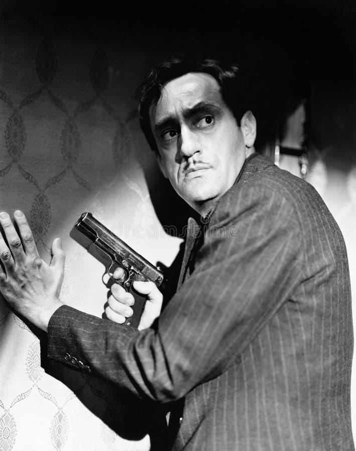 拿着手枪的匪徒的档案看在他的肩膀(所有人被描述不更长生存,并且庄园不存在 免版税库存照片