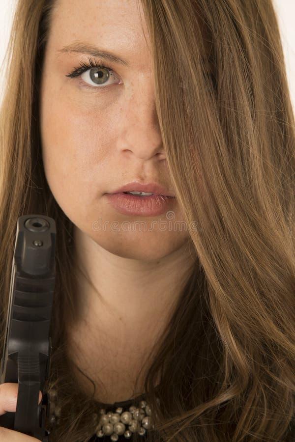 拿着手枪的美丽的妇女凝视通过她的头发 免版税图库摄影