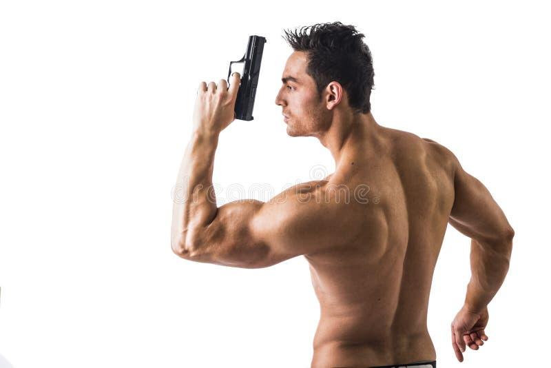 拿着手枪的运动露胸部的人反对白色 免版税库存照片