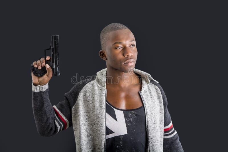 拿着手枪的年轻英俊的黑人 库存图片
