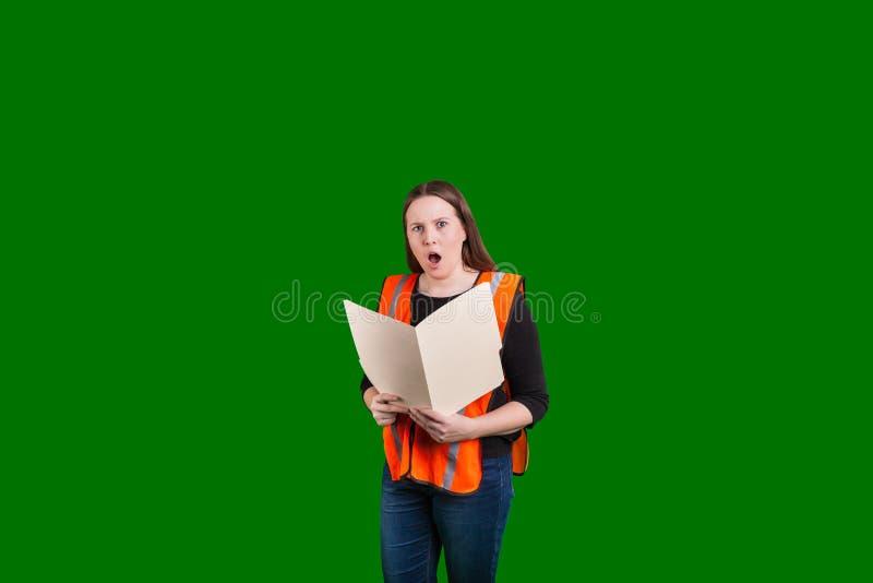 拿着打开文件文件夹的年轻的夫人使在她的穿橙色安全反射器背心的面孔的表示惊奇 库存图片