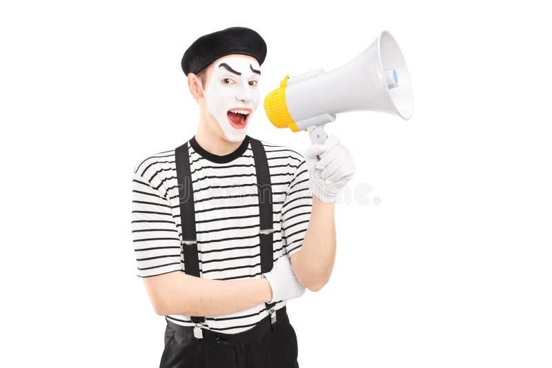 拿着扩音器和看照相机的一位男性笑剧艺术家 免版税图库摄影