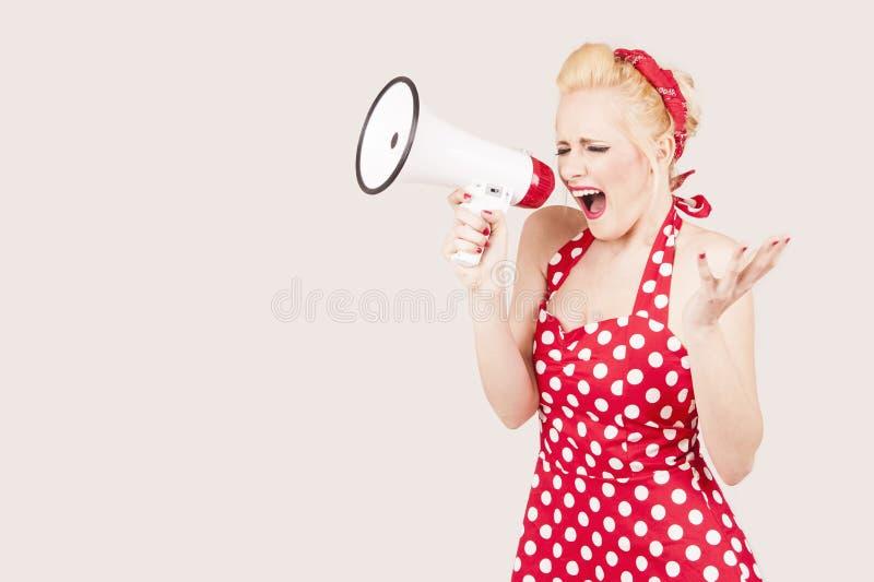 拿着扩音机的妇女画象,穿戴在画报样式红色礼服 库存图片