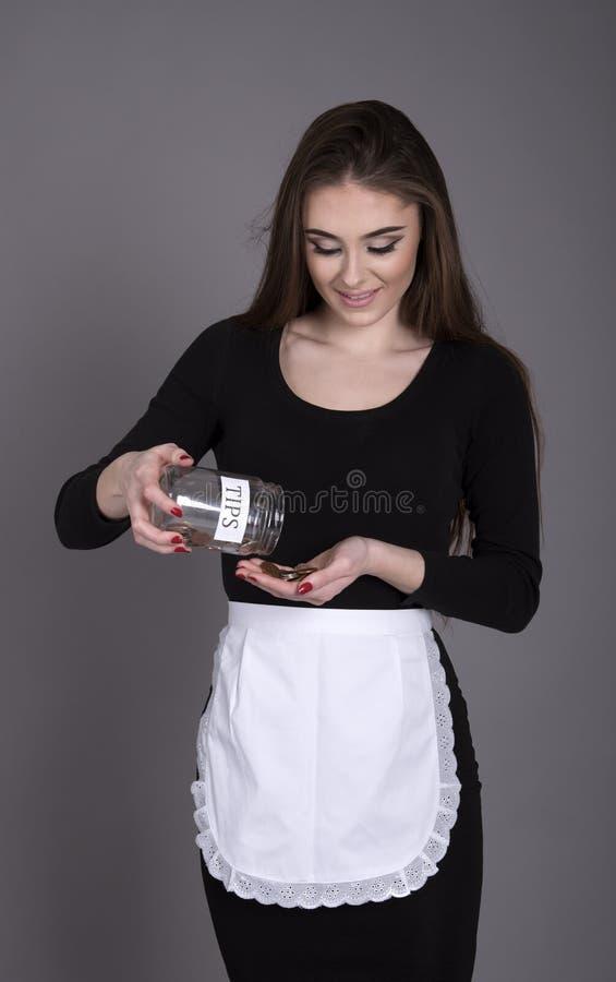 拿着技巧容器和计数现金的女服务员 库存照片