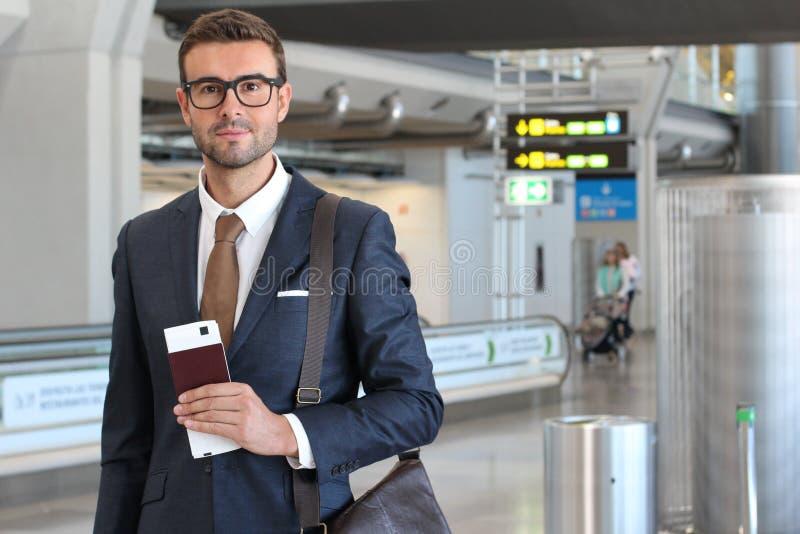 拿着护照和登舱牌的商人在机场 免版税图库摄影