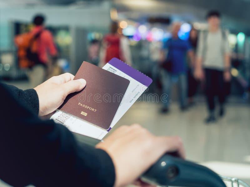 拿着护照登舱牌票被弄脏的人民的手移动 免版税库存照片