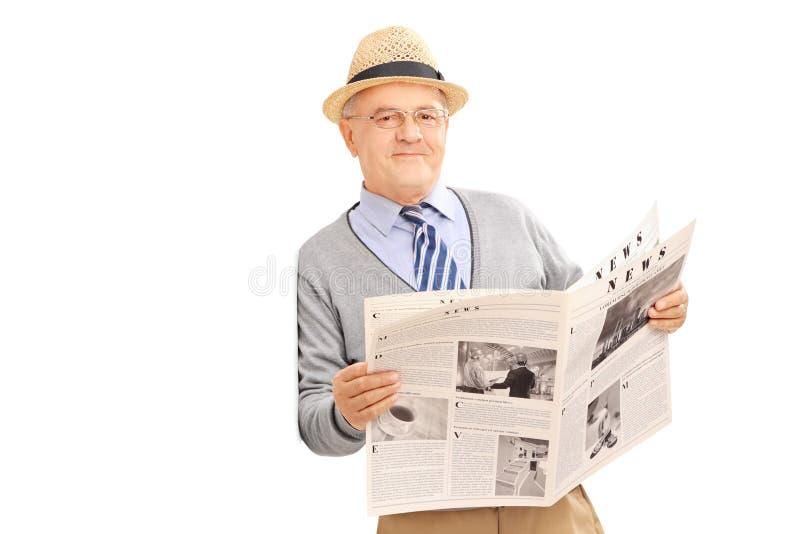 拿着报纸和倾斜对墙壁的资深绅士 库存图片