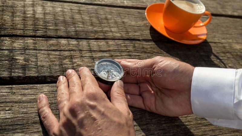 拿着指南针的一个人的手在橙色咖啡杯旁边 库存照片