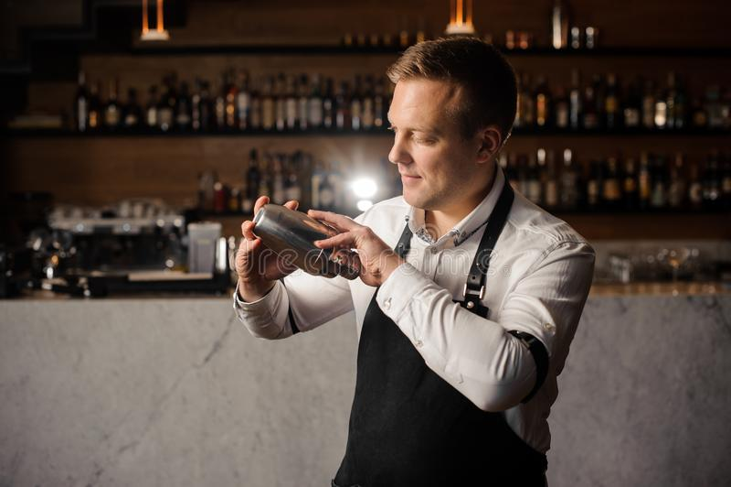 拿着振动器的一条白色衬衣和围裙的男服务员反对酒吧柜台 免版税库存图片