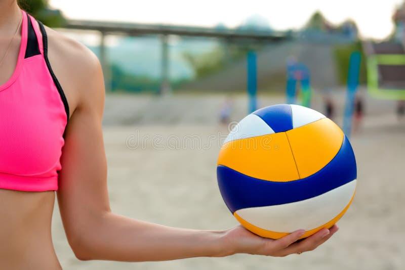 拿着排球球的美丽的运动女孩反对beac 免版税图库摄影