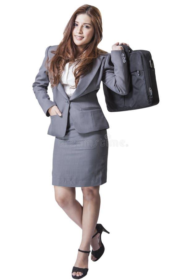 拿着提包的全长深色的女实业家 免版税库存照片