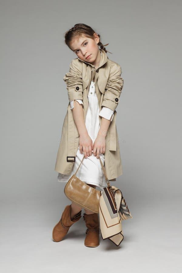 时尚小女孩佩带的军用防水短大衣 免版税库存图片