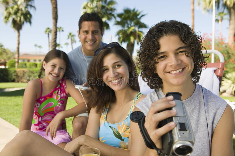 拿着摄象机的男孩(13-15)坐户外与姐妹(7-9)和父母画象。 库存照片