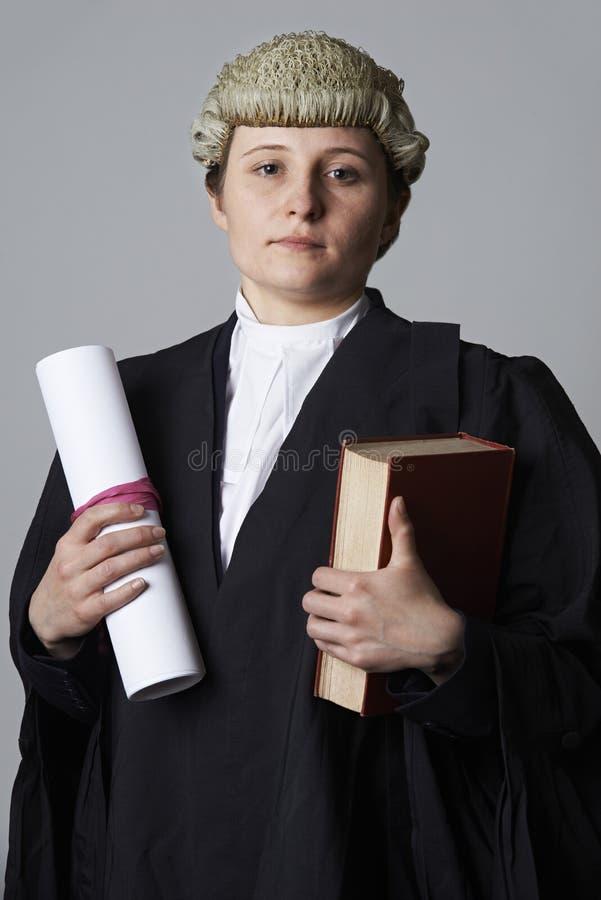拿着摘要和书的女性律师演播室画象 免版税图库摄影