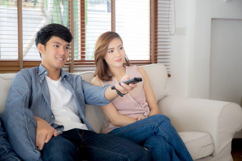 拿着放出在沙发的遥控的美好的年轻亚洲夫妇和看着电视或者录影与放松和愉快在客厅 库存照片