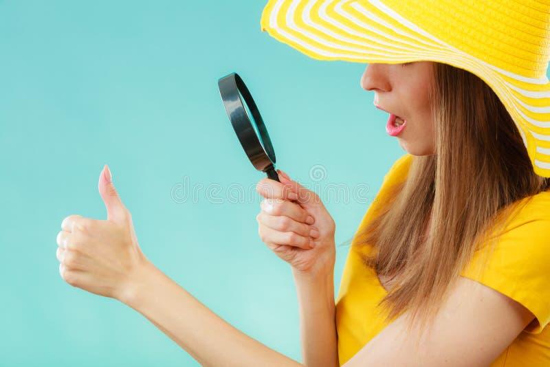 拿着放大镜的女孩看在指甲盖 免版税库存图片