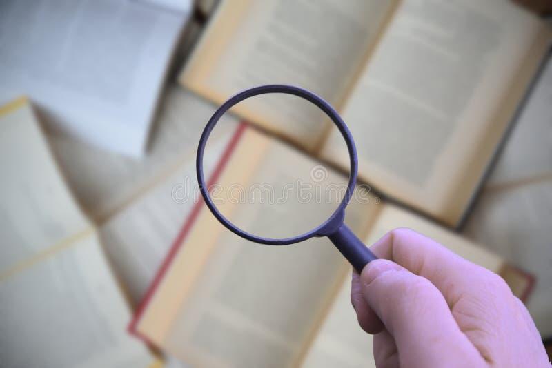 拿着放大镜的手,当搜寻信息时 免版税库存照片