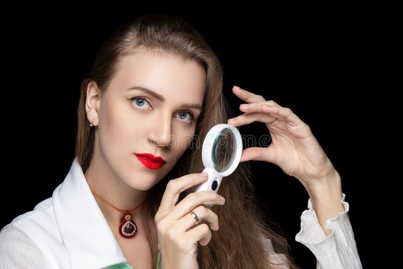 拿着放大镜的美女医生 图库摄影