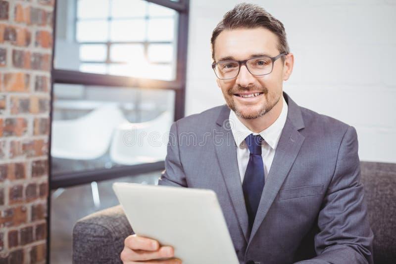 拿着数字式桌的微笑的商人画象,当坐沙发时 免版税库存照片