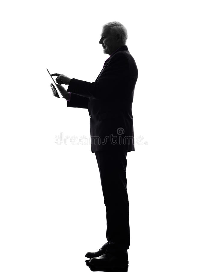 拿着数字式片剂剪影的资深商人 免版税图库摄影