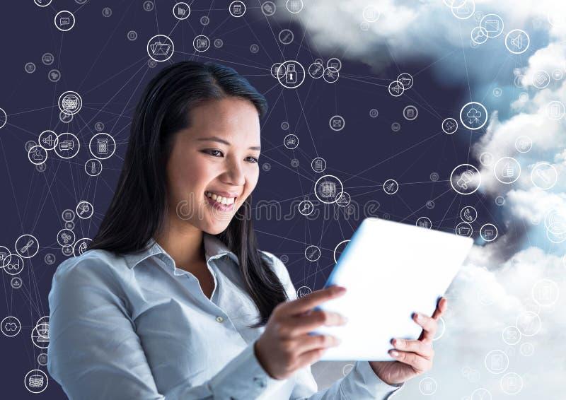 拿着数字式片剂和连接象的愉快的妇女用云彩在背景中 免版税库存图片