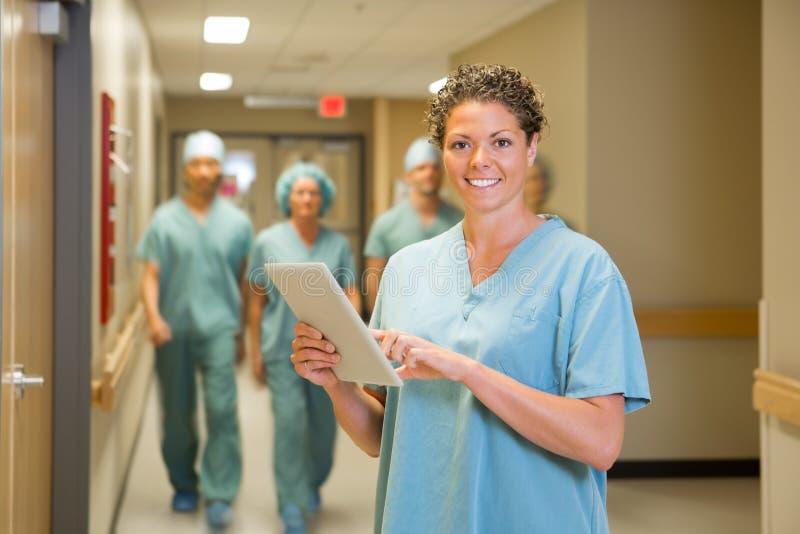 拿着数字式片剂的外科医生在医院 免版税库存照片