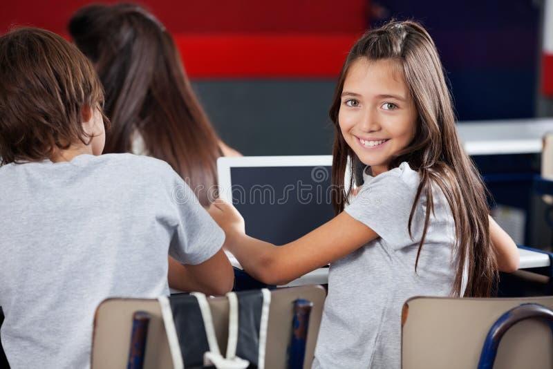 拿着数字式片剂的女小学生在书桌  免版税图库摄影