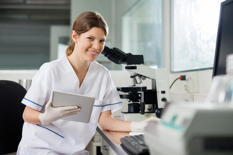 拿着数字式片剂的女性科学家在实验室 库存照片