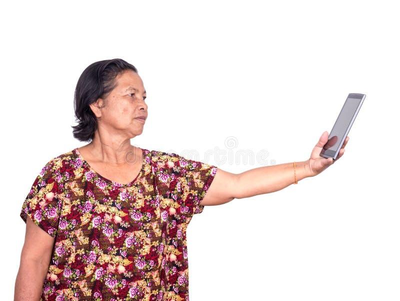 拿着数字式片剂的年长亚裔妇女和延长forw 库存照片