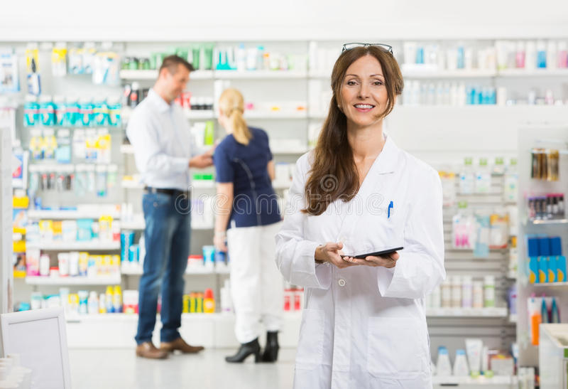 拿着数字式片剂的微笑的女性化学家在 免版税图库摄影
