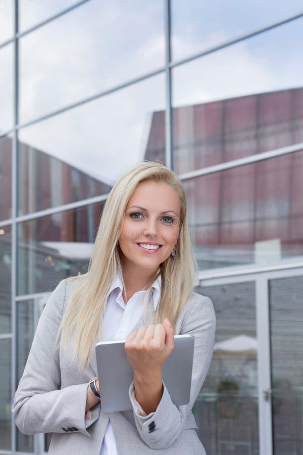 拿着数字式片剂的愉快的女实业家画象反对办公楼 图库摄影
