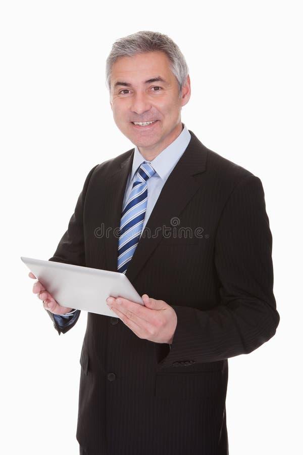 拿着数字式片剂的成熟商人 库存图片