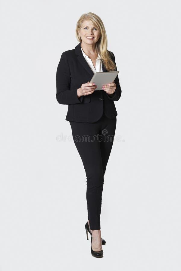 拿着数字式片剂的成熟女实业家演播室画象 免版税库存照片