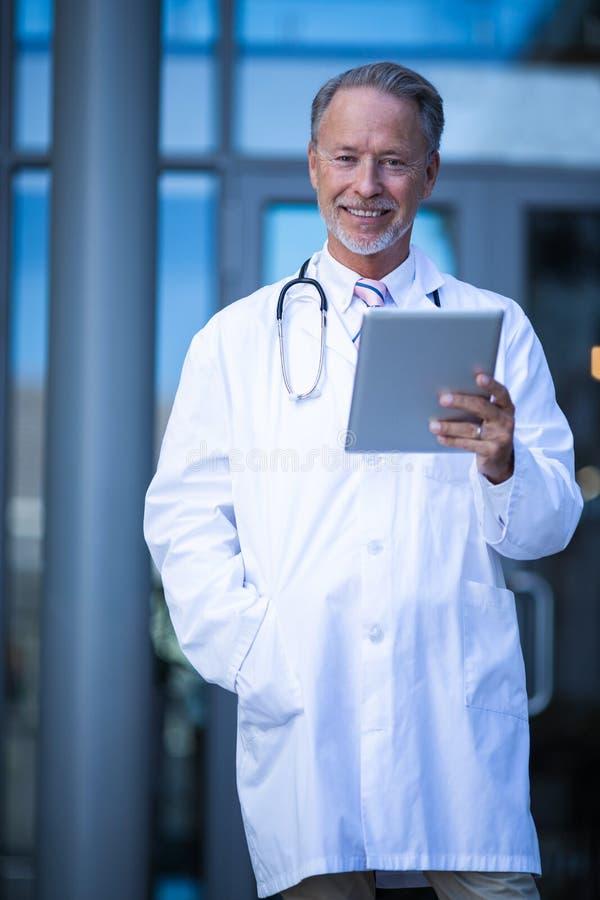 拿着数字式片剂的男性外科医生 库存图片