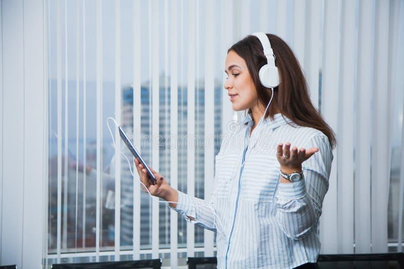 拿着数字式片剂的白色耳机的俏丽的微笑的女实业家 免版税库存照片