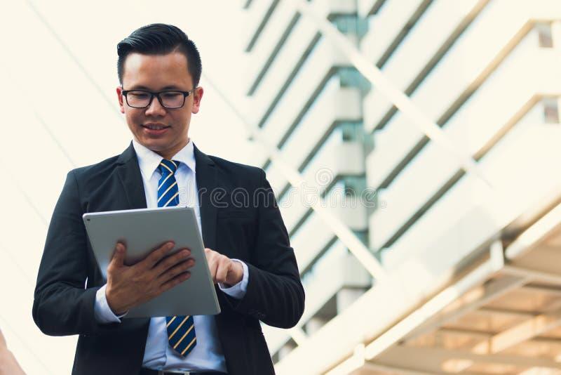 拿着数字式片剂的确信的现代年轻商人穿戴黑色衣服手画象  专业商人 库存照片