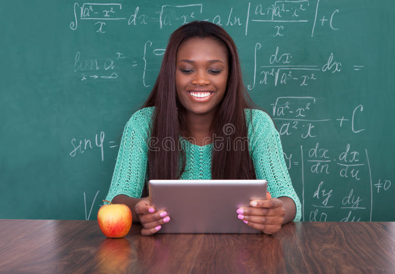 拿着数字式片剂的老师在学校书桌 库存图片