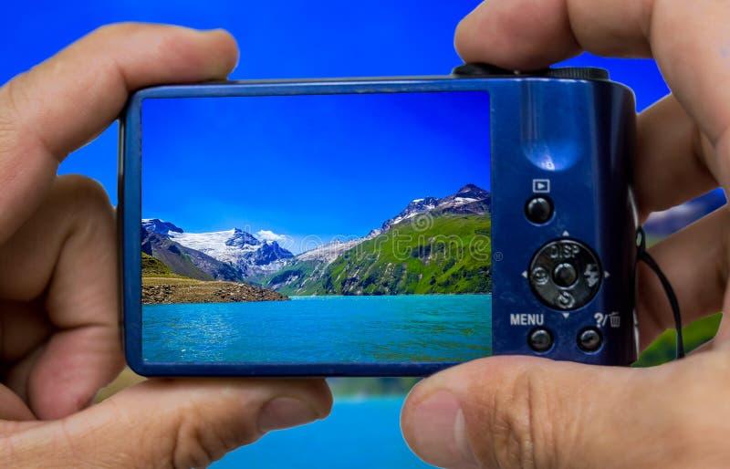 拿着数字照片照相机的旅游手在度假 卡普伦水库-人工湖Mooserboden,奥地利 免版税库存图片